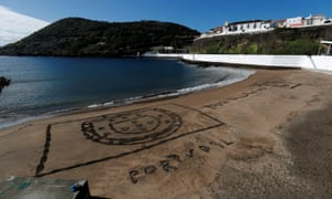 Portugal's coat of arms is seen carved in sand on a beach in Angra do Heroismo on the Azores islands, Portugal.
