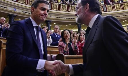 Pedro Sanchez shakes hands with Mariano Rajoy.