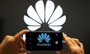 The Huawei logo being photographed by a mobile phone