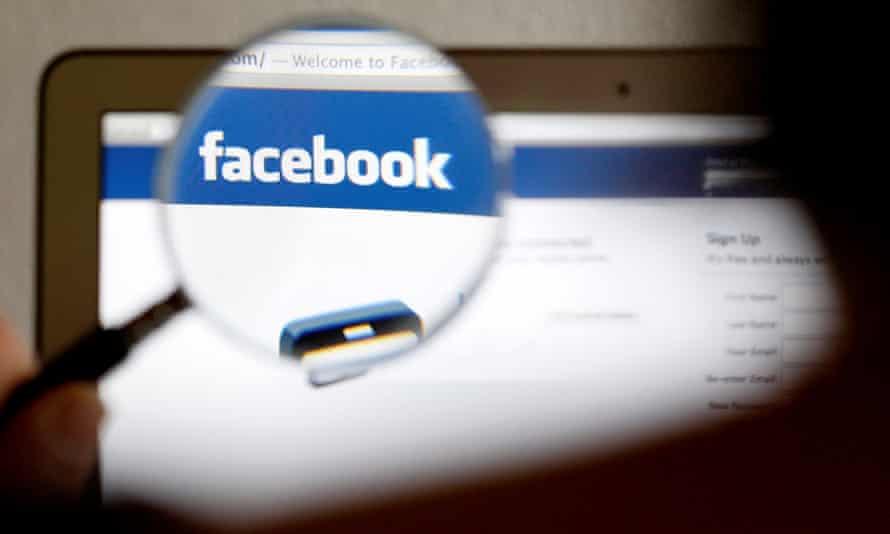 a Facebook logo on a computer screen is seen through a magnifying glass
