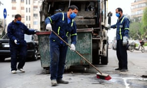 Workers clean a street in Damascus