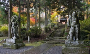 Two fearsome stone figures at the foot of tree-lined stone stairs leading up to the Futago-ji temple