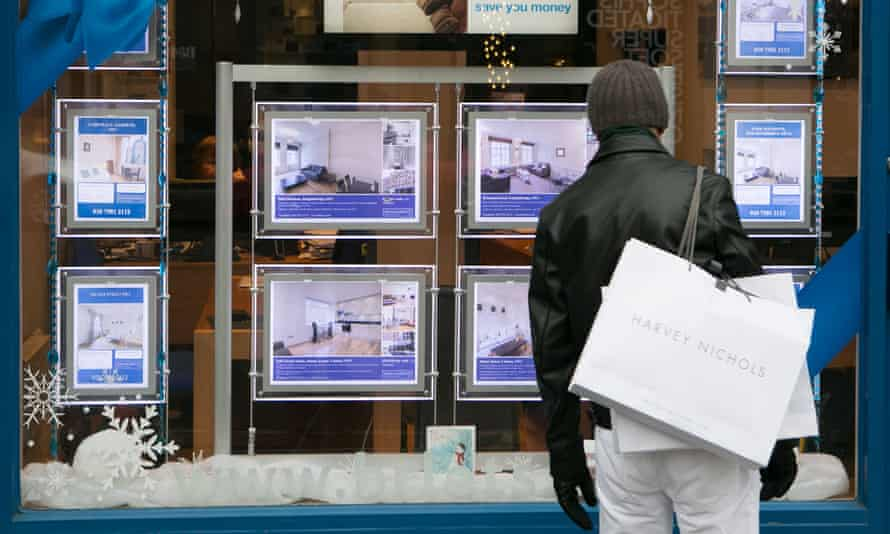 A man looks in an estate agent's window