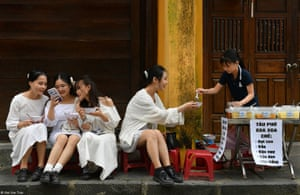 Four girls sat on a kerb next to a soup seller