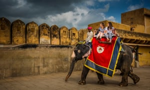 Elephants carry tourists along the walls of the Amber Fort in Jaipur, India.