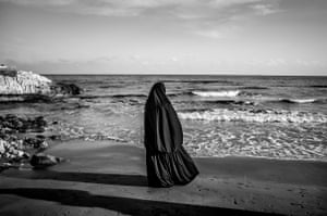 A Syrian woman looks at the sea in Kizkalesi, Turkey where thousands of refugees land, hoping to embark on ships headed to Europe.