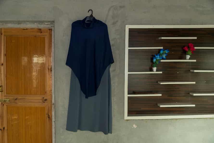 Aizar's uniform hangs on a wall since schools closed again.