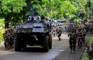 An armoured personnel carrier and government troops are seen marching towards Marawi
