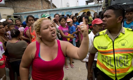 A woman argues with police as tensions rise among people waiting for more than an hour for free food and water from the government.