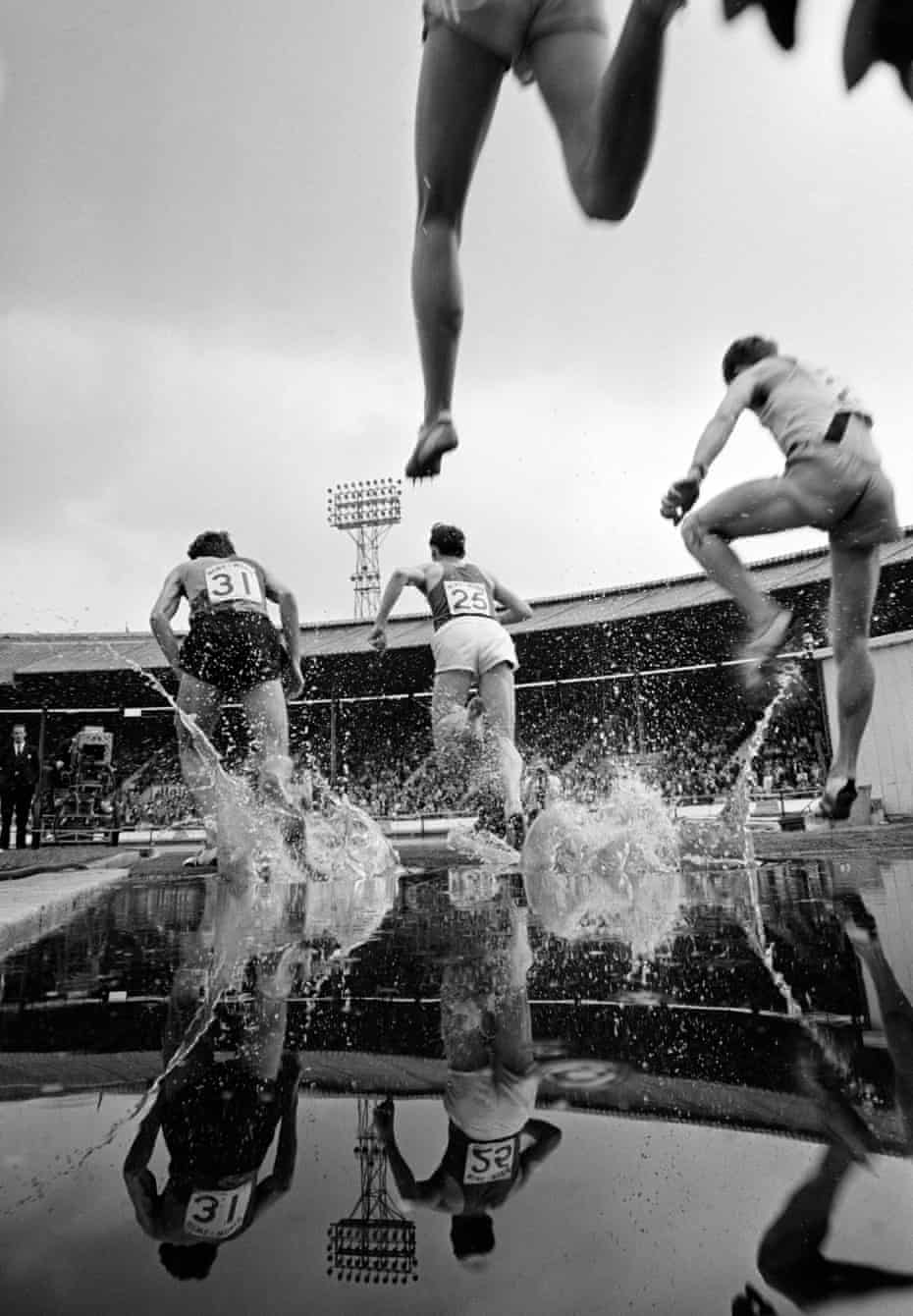 Athletes race through the water jump during the men's steeplechase at the British Games in 1965.