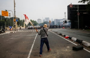 A demonstrator holds an Indonesian flag in front of police officers during a protest against the government's proposed labour reforms in a controversial jobs creation bill in Jakarta.