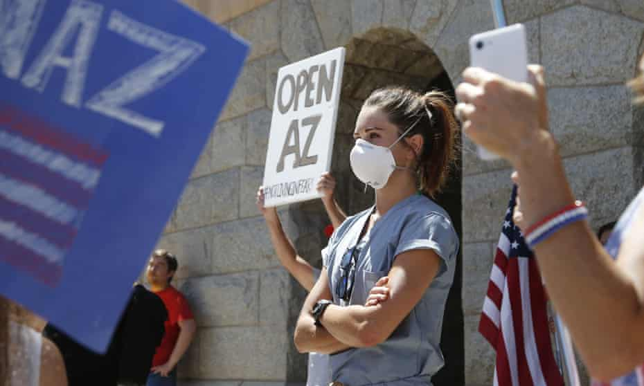 """A healthcare worker stands in counter-protest to the """"Re-open Arizona"""" rally around her."""