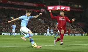 John Stones tries to clear with Roberto Firmino in pursuit.