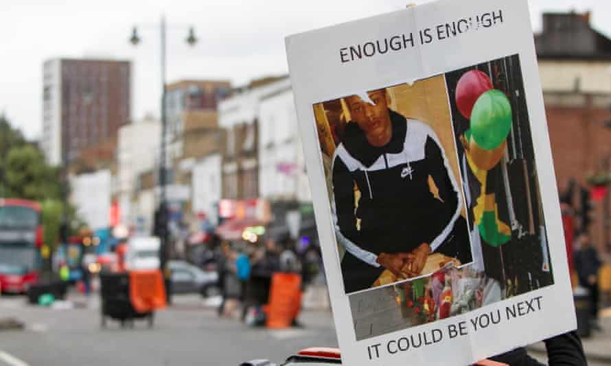A banner showing Rashan Charles at a protest against his death.