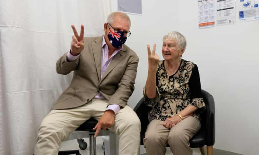 Australian prime minister Scott Morrison gives the V for victory sign with Jane Malysiak, 84, who was Australia's first recipient of a Covid-19 vaccination