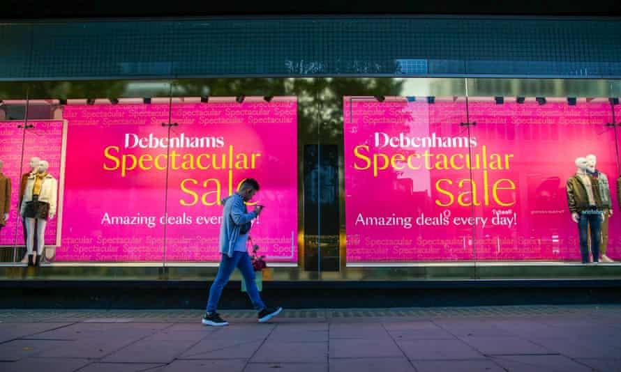 A man walks past a Debenhams winter sale window display on Oxford Street in central London