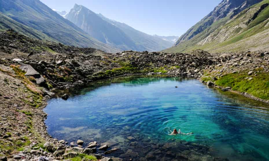 Someone swimming in a turquoise rock pool, mountain peaks behind