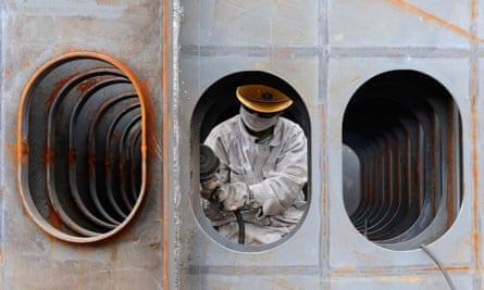 A worker polishes steel plate at a dockyard in Wuhu, Anhui , China