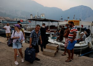 Tourists board a boat during evacuation as a wildfire approaches Turunc village in Marmaris district, Turkey