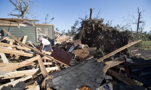 David Maynard sifts through the rubble searching for his wallet in Onalaska, Texas, on Thursday after a tornado destroyed his home the night before.