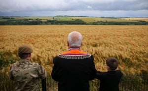 Former RUC officer Cecil Haire and his grandchildren gaze over a poppy field at Thiepval