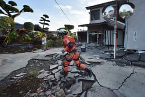 A member of a rescue team runs on a street cracked by the earthquake in Mashiki