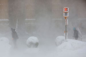 Workers shovel at the entrance to City Hall in whiteout conditions during a winter storm in Buffalo, New York
