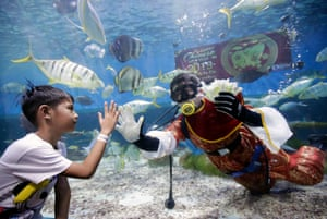 A diver wearing a Chinese traditional costume feeds fishes on the eve of Chinese Lunar New Year at the Oceanarium of the Manila Ocean Park