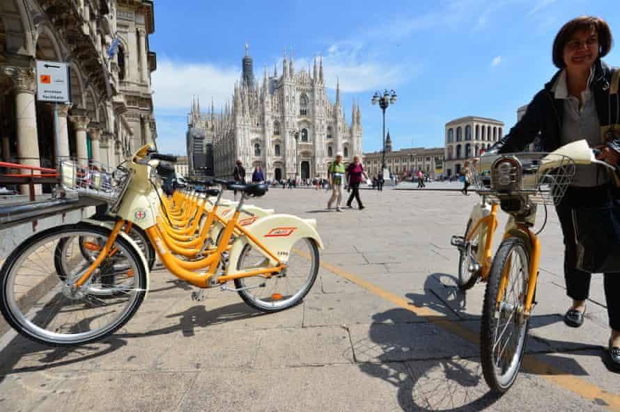 Cyclist using public bike share, Milan.