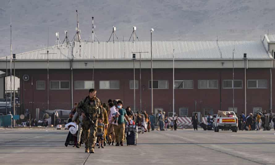 A US air force airman guides evacuees to board a plane at Hamid Karzai international airport in Kabul on Tuesday.
