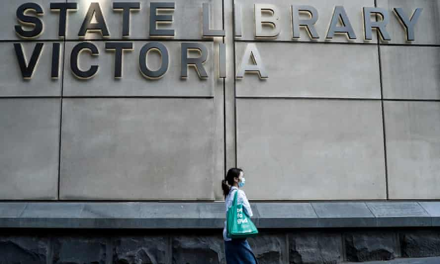 a woman in a mask walks in front of the state library of victoria