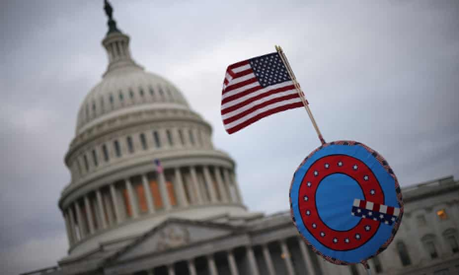 Supporters of Donald Trump fly a US flag with a symbol from the group QAnon as they gather outside the US Capitol before their deadly assault on 6 January.