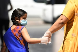 A mother and daughter, wearing protective gloves and face masks, walk together in the Emirate city of Dubai on Tuesday