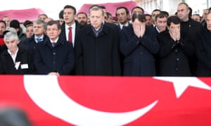 President Erdoğan (centre) mourns during the funeral of a police officer  killed in Saturday's bomb attacks