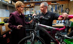 First Minister of Scotland and leader of the Scottish National Party Nicola Sturgeon MSP adjusts a bike with cycling mechanic Gerardo Ballesteros during a general election campaign visit at The Bank Cafe Bike Hub in Neilston, on the outskirts of Glasgow