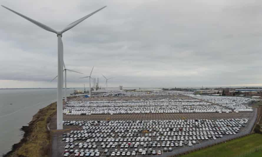 New cars in a compound next to wind turbines in Sheerness, Kent.