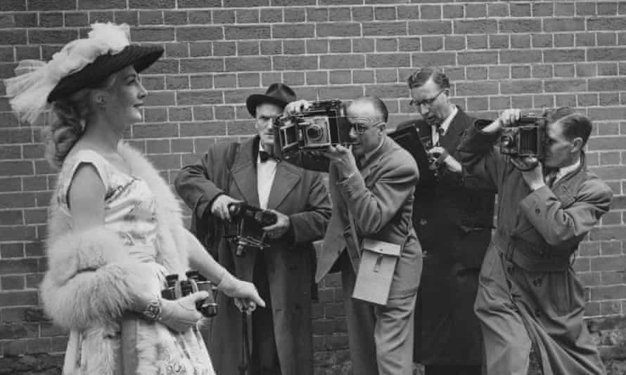 A woman with a nylon straw hat poses for photographers at Ascot, 1956.