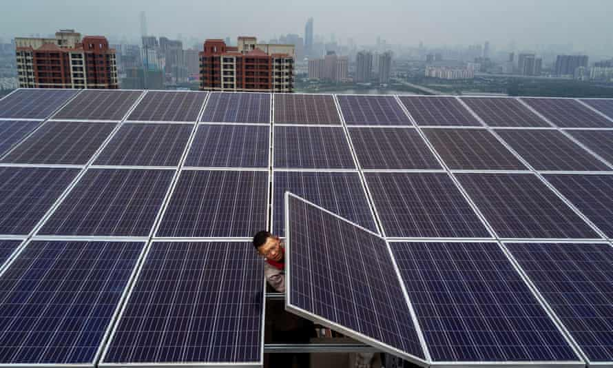 A man adjusts a solar panel on the roof of a 47-storey building in Wuhan, China.