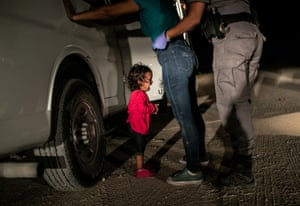 Child cries as mother is searched by US border patrol.