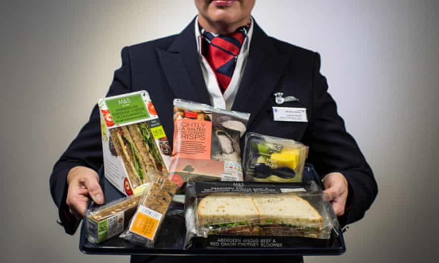 A BA cabin crew member holds up the new M&S menu