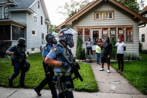 Protesters and residents watch as police in riot gear walk down a residential street, 28 May 2020, in St Paul, Minneapolis
