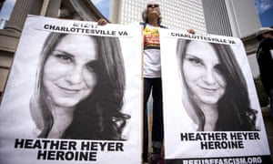 A demonstrator holds signs featuring Heather Heyer at a rally in Chicago, IL the day after white nationalists attacked counter-protesters in Charlottesville in 2017.