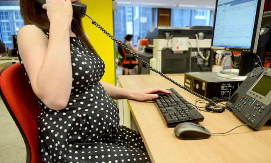 Pregnant woman working at office desk.