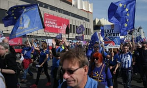 Anti-Brexit campaigners march along the seafront outside the Labour conference holding placards and waving European and Union flags.