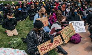 High school students from across Minneapolis sit in silence during a statewide walkout demonstration on Monday