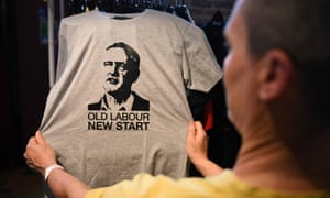 A supporter of Momentum looks at a T-shirt showing Corbyn's face during the Labour party conference in Liverpool.