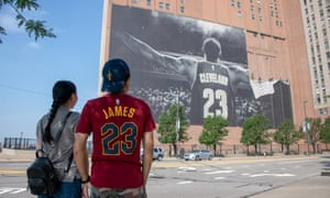 Workers remove Nike's LeBron James banner from the Sherwin-Williams building near Quicken Loans Arena