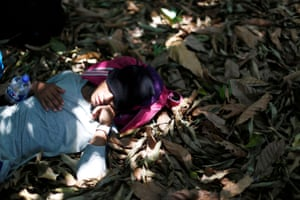 A man belonging to a caravan of migrants from Honduras sleeps in a forest by a highway in Tuxtla Chico.