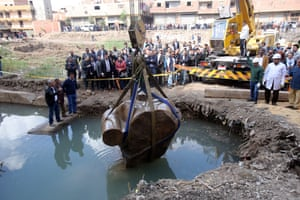 Workers look on as a crane lifts parts of a statue unearthed in Cairo, Egypt