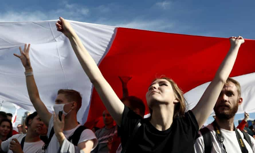 Opposition supporters carry a huge flag of the pre-Soviet republic of Belarus